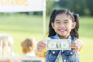Young Girl holding dollar bill next to lemonade stand