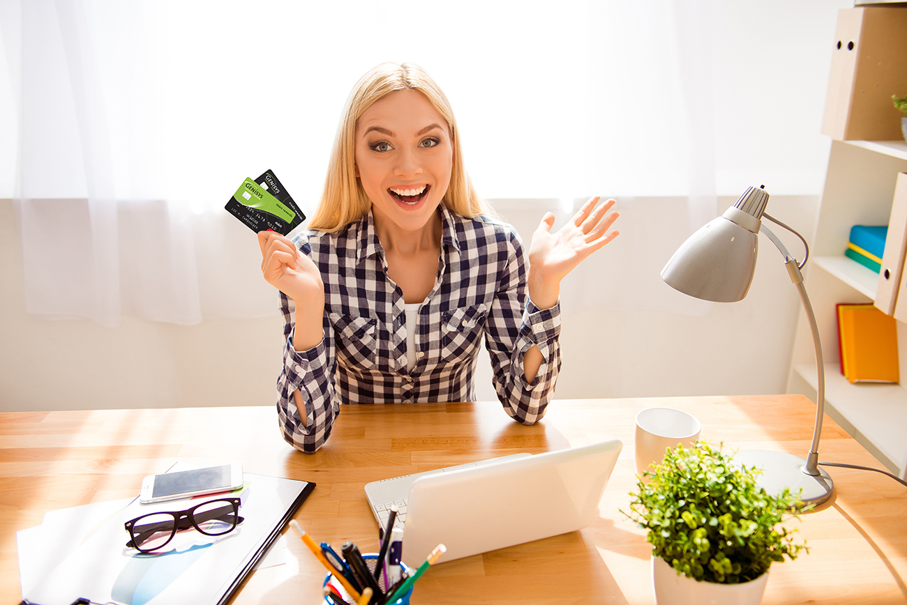 Woman sitting at desk holding Genisys Debit and Credit Mastercard
