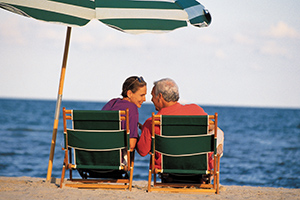 Mature couple smiling at each other sitting on chairs at beach
