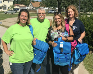 Genisys and Macomb Community Action Staff with Donated Backpacks