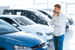 Young adult in car showroom looking at cars