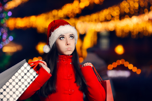 Woman with stressed look with holiday shopping bags