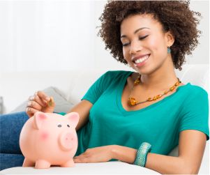 Young woman saving money with piggy bank