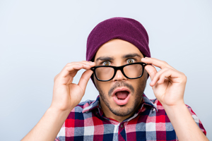 Young guy holding eyeglasses with shocked expression