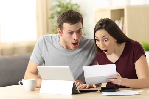 Couple looking at bills surprised