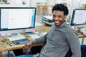 Young man sitting infront of his computer smiling
