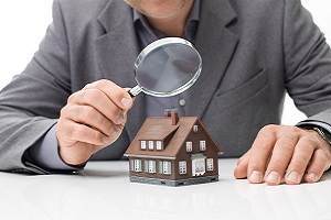 Man holding magnifying glass over model of a  home
