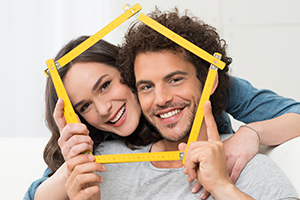 Couple holding structure of house around faces