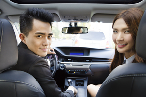 Young couple in a car looking towards backseat