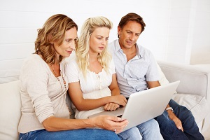Couple with daughter looking at accounts on laptop