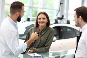 Woman at dealership with two salesman to find out if she can get a car
