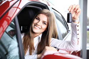 Young woman holding keys in her new car