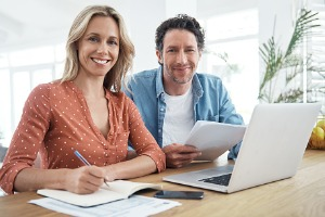 Couple smiling at camera with paperwork
