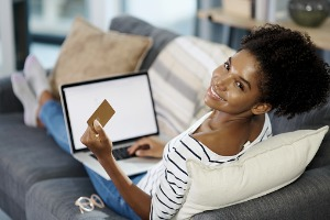 Woman sitting on couch online shopping with credit card