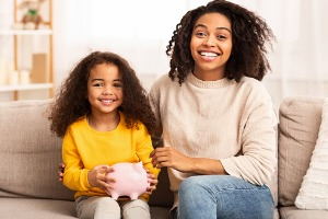 Mother and daughter smiling on couch with piggy bank in hand