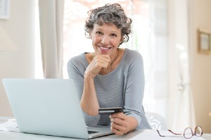 Adult woman sitting at computer with credit card in hand.