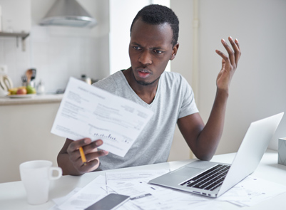 Man looking at bills and frustrated with budget