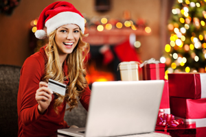 Woman in santa hat holiday shopping with credit card