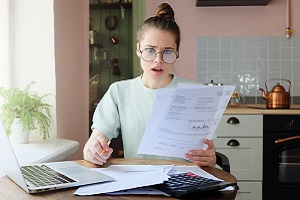 Young Woman Looking at Paperwork with a Shocked Expression