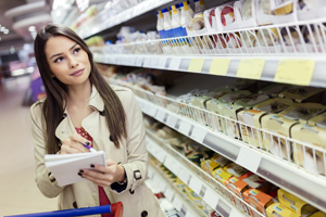 Woman in supermarket with shopping list
