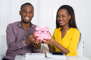 Happy Couple holding a piggy bank