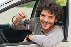 Young man sitting in car, smiling and holding up a set of keys.