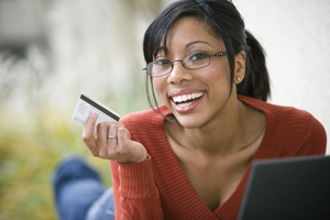 Young woman using credit card to shop online