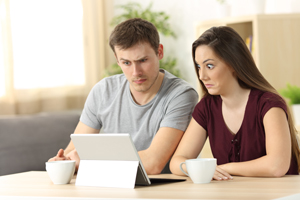 Couple reading iPad looking confused