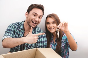 Young couple holding keys to new house