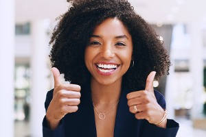 Woman smiling and holding two thumbs up