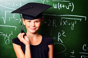 Young girl in graduation cap in front of chalkboard
