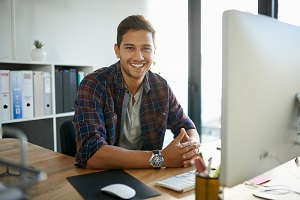 Man smiling with hands clasped in front of computer