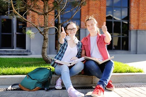 2 students sitting outside school with thumbs up