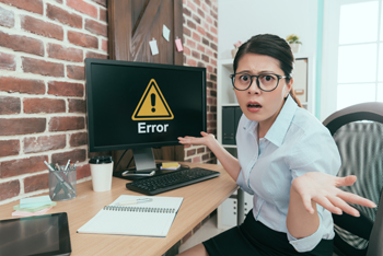 Woman looking at Error Message on Computer screen