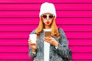 Young Woman Looking at Phone with Sunglasses and Coffee in hand