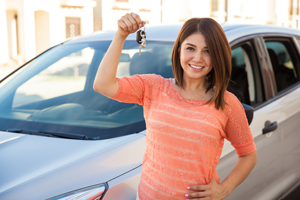 Young woman holding set of keys to new car
