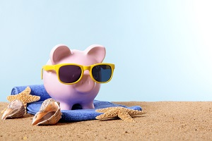 Piggy bank with sunglasses on beach