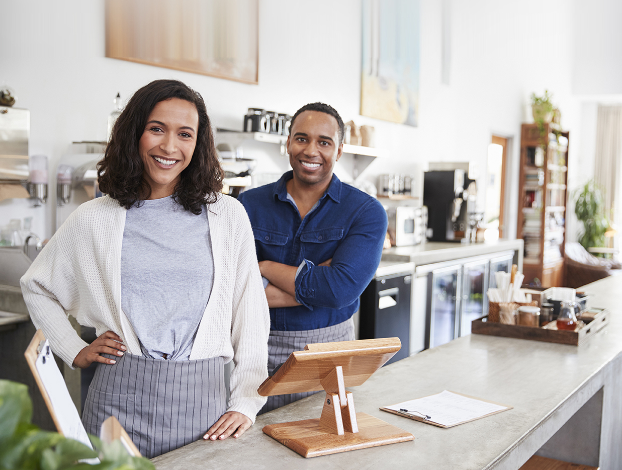 Woman and man business owners standing near sales register