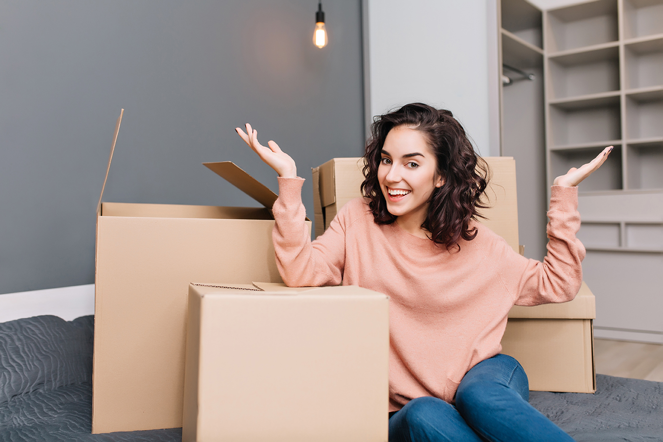 image of woman sitting on the floor with moving boxes