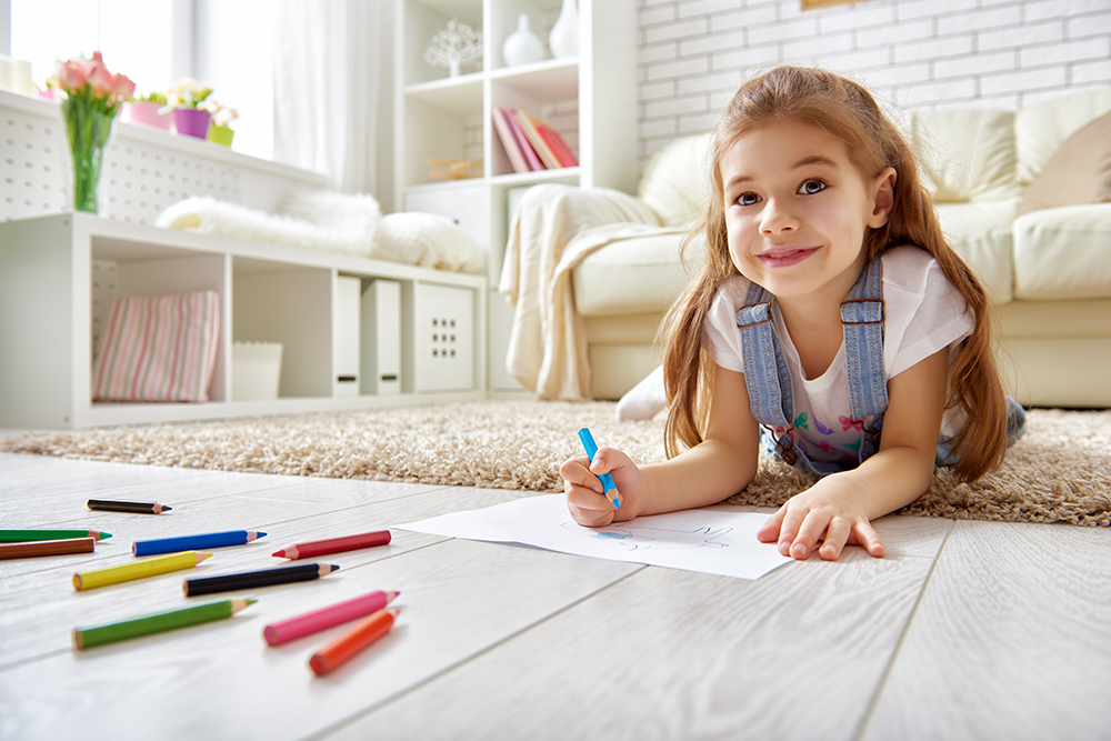 Happy young girl coloring with pencils